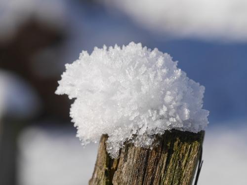 Schnee auf Holzpfosten